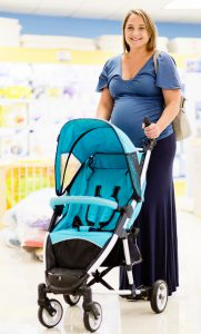 A very pregant wman smiles beautifully as she chooses a pushchair in a specialist baby shop.