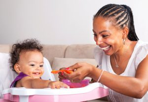 African-American Mother Feeding Baby Girl In High Chair