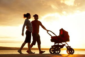 Silhouettes of happy parents walking with stroller on the seacoast