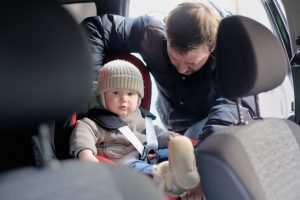 Father fasten his toddler son in car seat