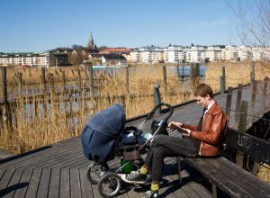 A father with a pram is sitting by the seaside with a beautiful view over Stockholm.See also my LB;