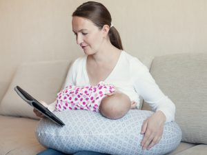 Happy mother breast feeding her newborn in room, indoor