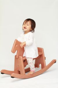 Japanese baby girl playing with rocking horse (0 year old)