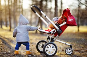 Toddler boy playing with his stroller walking outdoors at the warm spring day